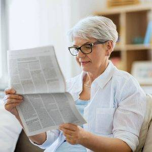 age and people concept happy senior woman reading newspaper at